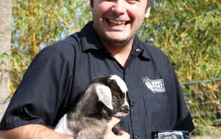 Abernathy from Grumpy Goat Coffee holding a goat